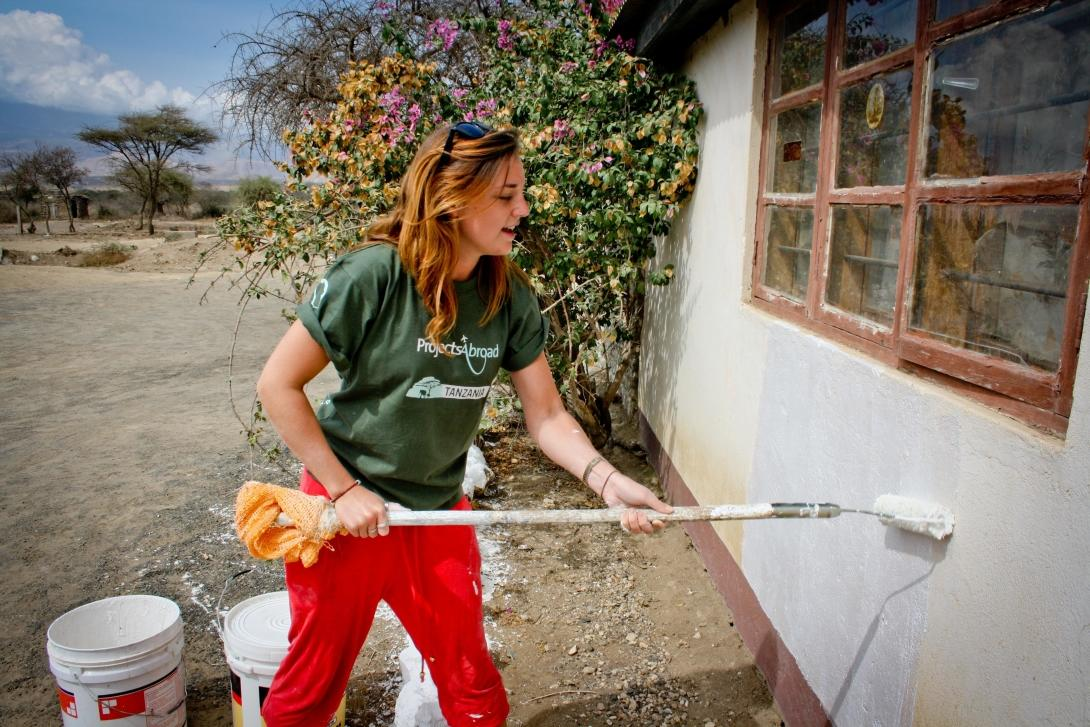 A Building volunteers adds a coat of paint to a newly built classroom in Tanzania